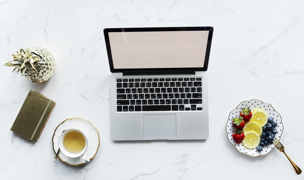 Download Free Stock HD Photo of Overhead view of a laptop on white marble surface with snacks and beverage Online