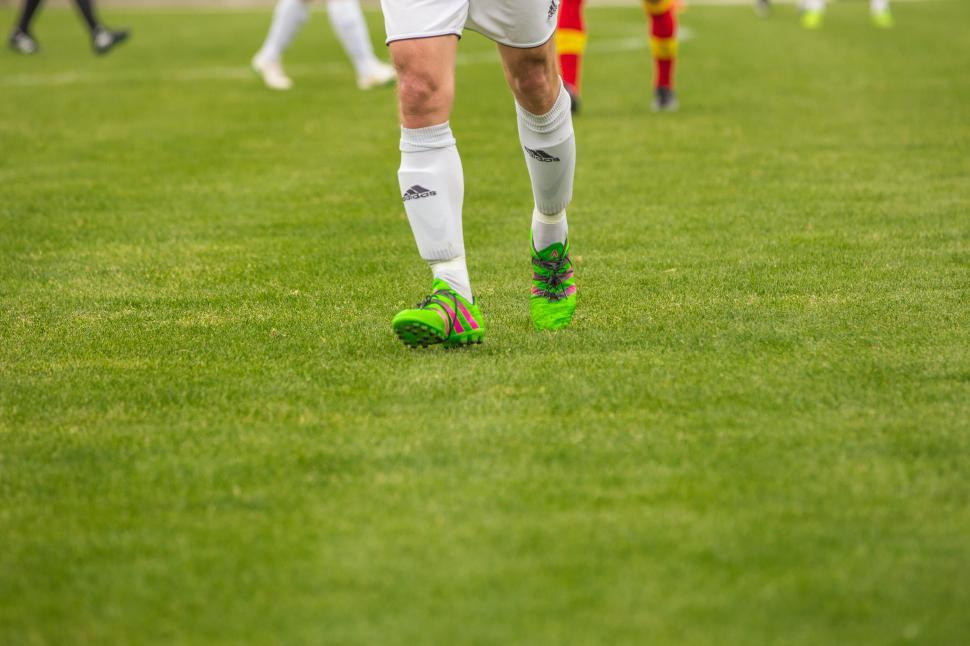 Download Free Stock HD Photo of Footballer legs and green shoes on ground Online