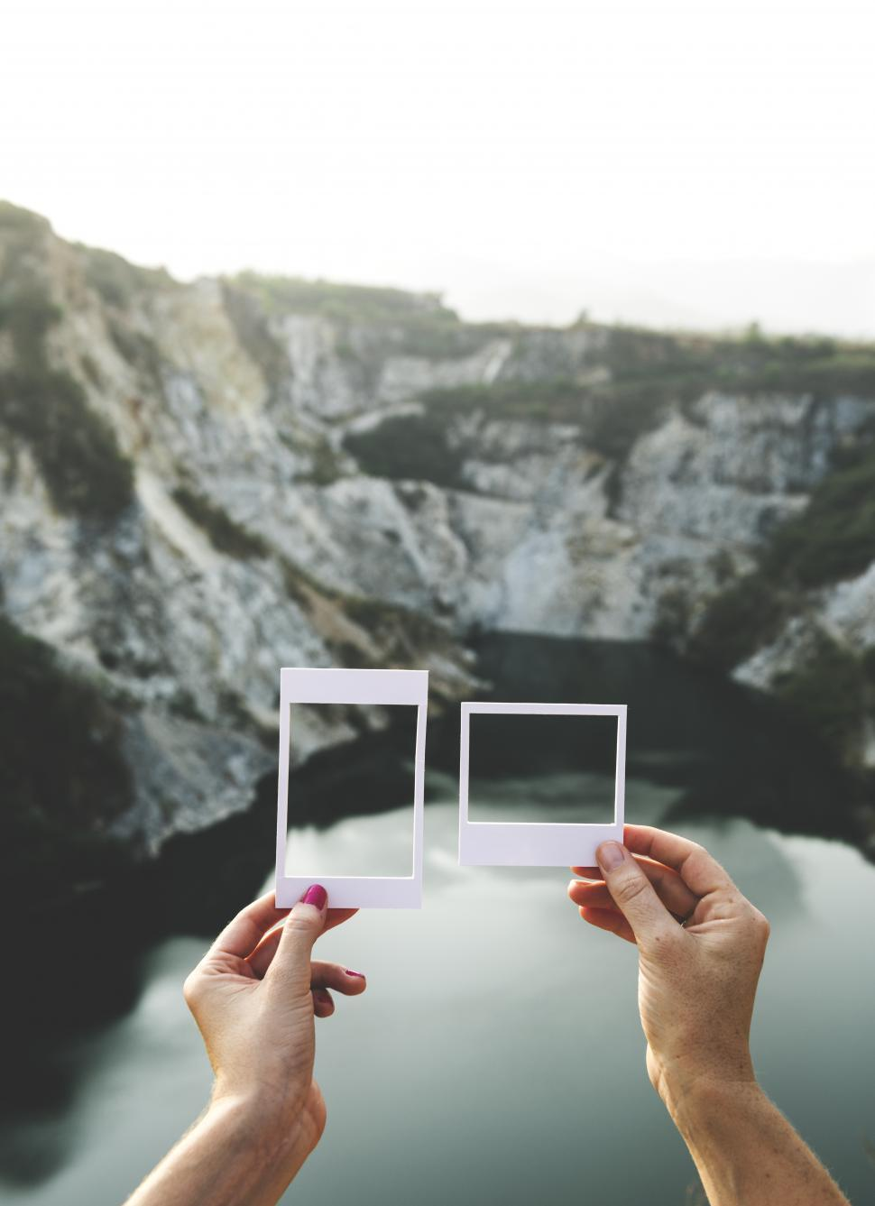 Download Free Stock HD Photo of Hands holding a photo frame shaped paper cut out templates in front of mountains Online
