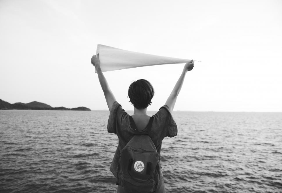 Download Free Stock HD Photo of A young woman holding white flag high - in black and white Online