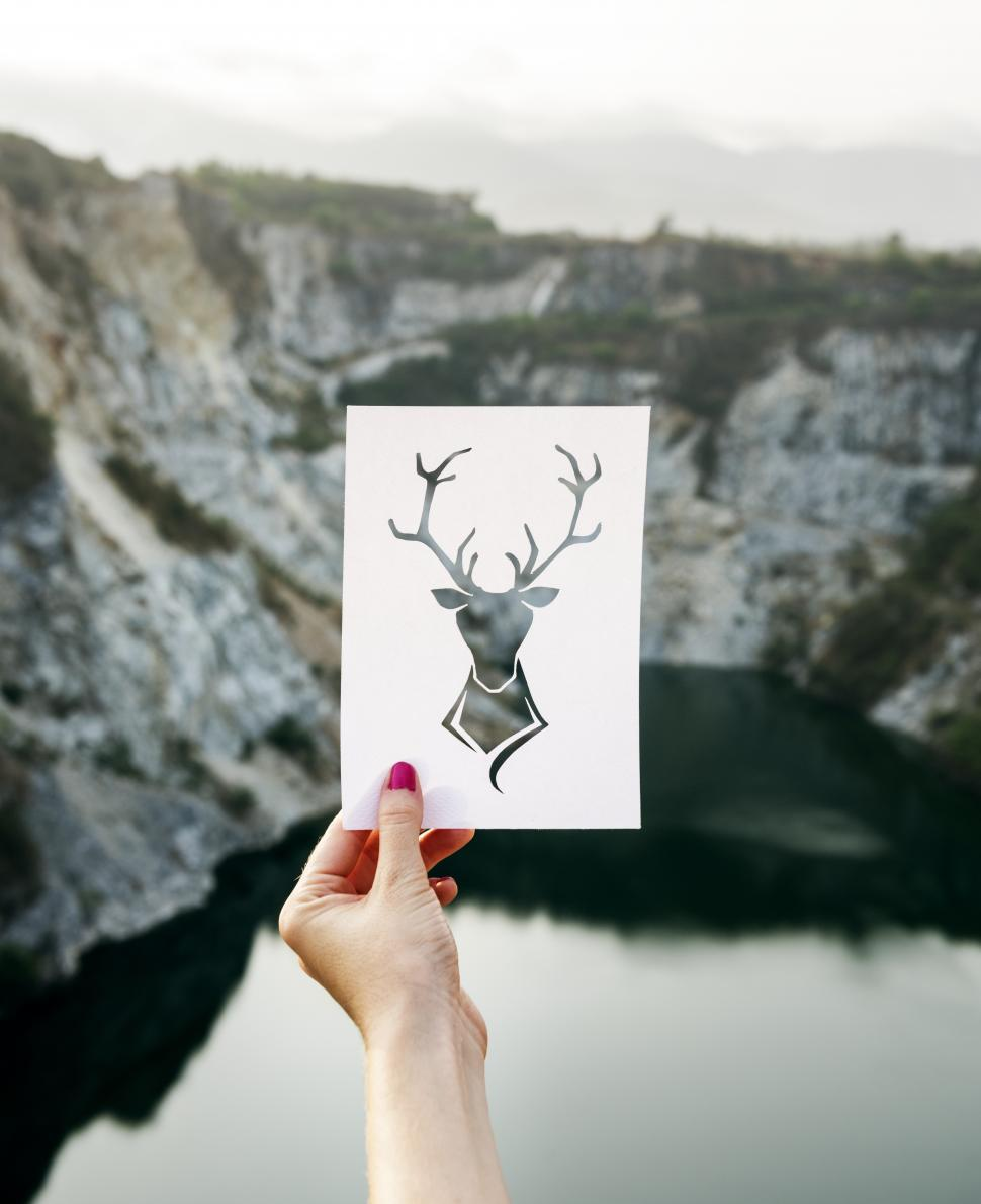 Download Free Stock HD Photo of A hand holding a stag shaped paper cut out template Online