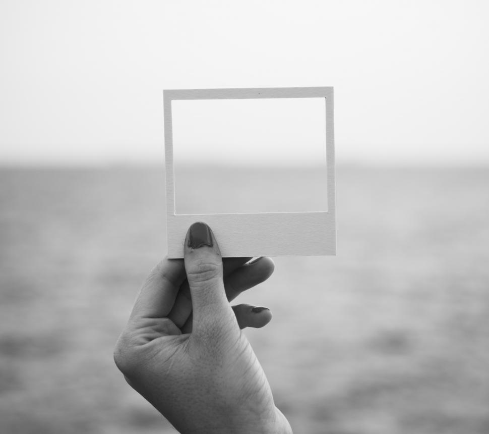 Download Free Stock HD Photo of A hand holding a photo frame shaped paper cut out Online