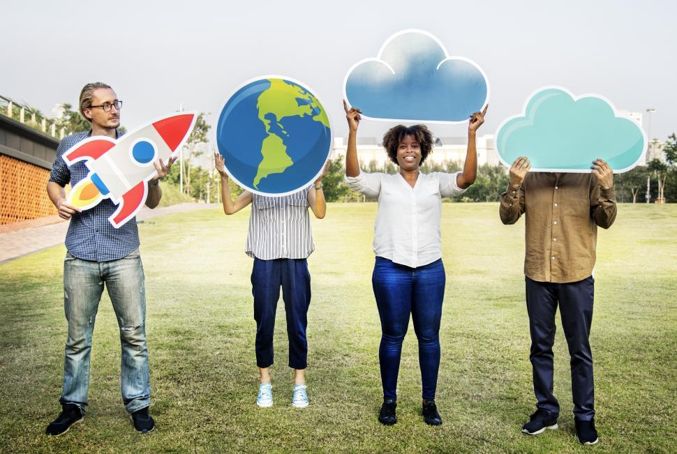 Download Free Stock HD Photo of A group of volunteers posing with a globe, a rocket and cloud shaped cardboard cutouts Online