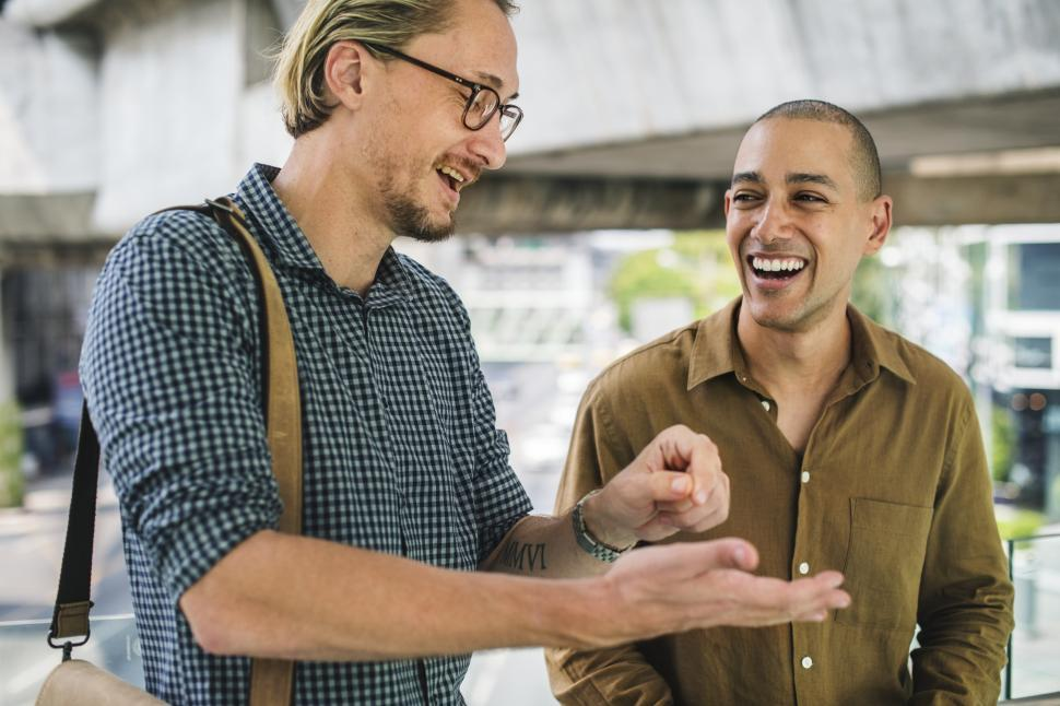 Download Free Stock HD Photo of Two smiling young men talking to each other Online