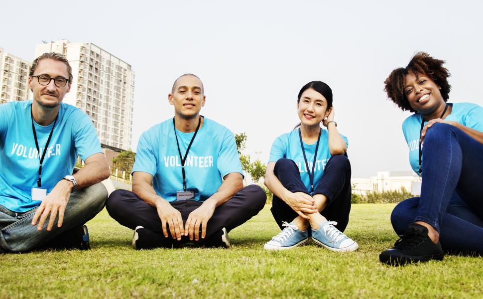 Download Free Stock HD Photo of A group of volunteers sitting on the grass Online