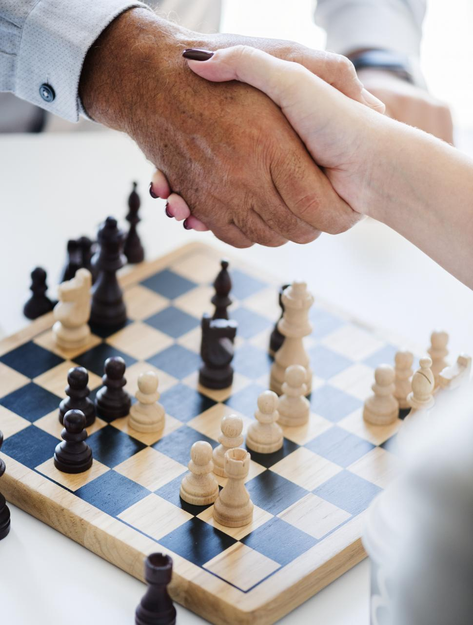Download Free Stock HD Photo of Close up of a handshake over a chessboard after game Online