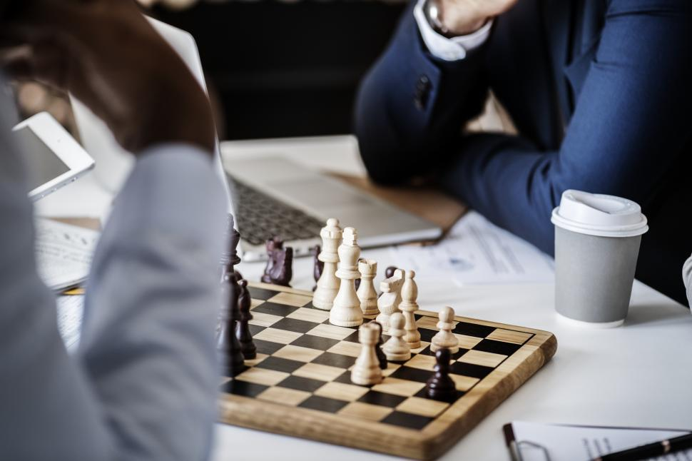 Download Free Stock HD Photo of Close up of people pondering a chess board Online