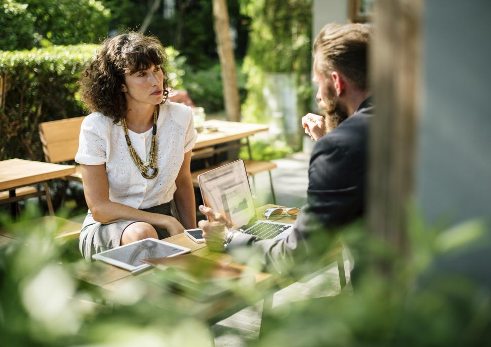 Download Free Stock HD Photo of View of two people talking at an outdoor restaurant table Online