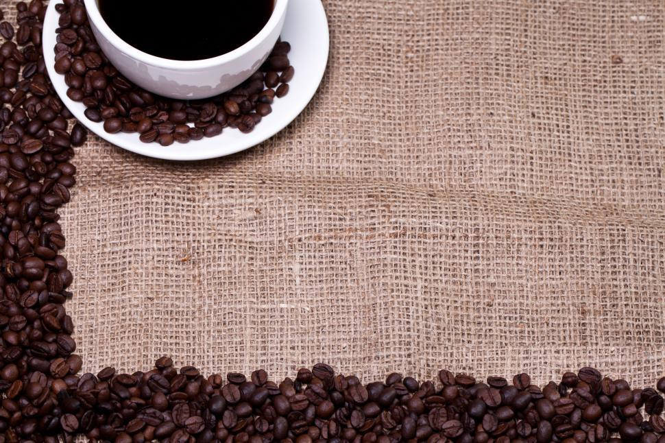 Cup of hot coffee in burlap background, framing copyspace