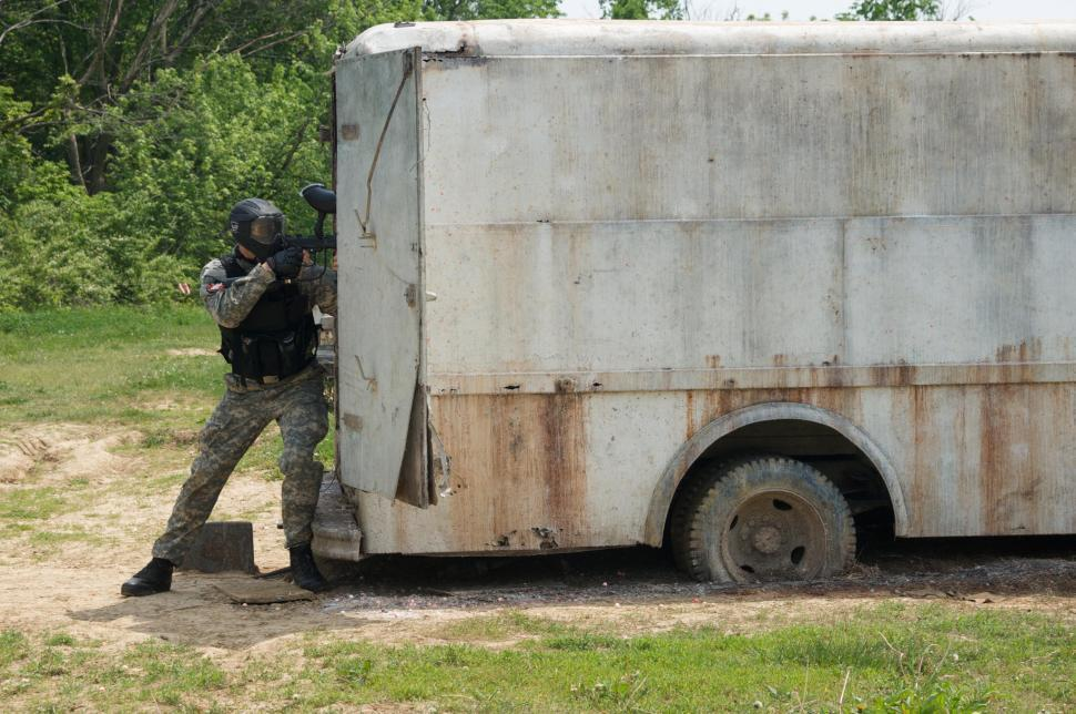 Download Free Stock HD Photo of Junkyard paintball game with camouflaged man  Online