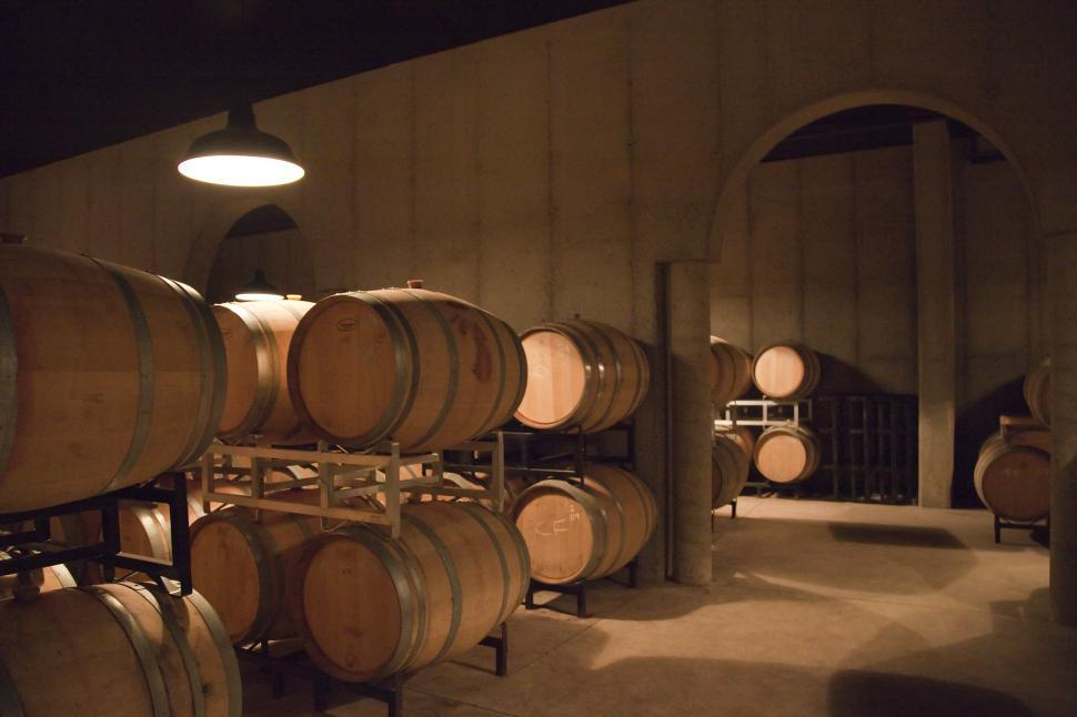 Free image of Wine aging in oak barrels.