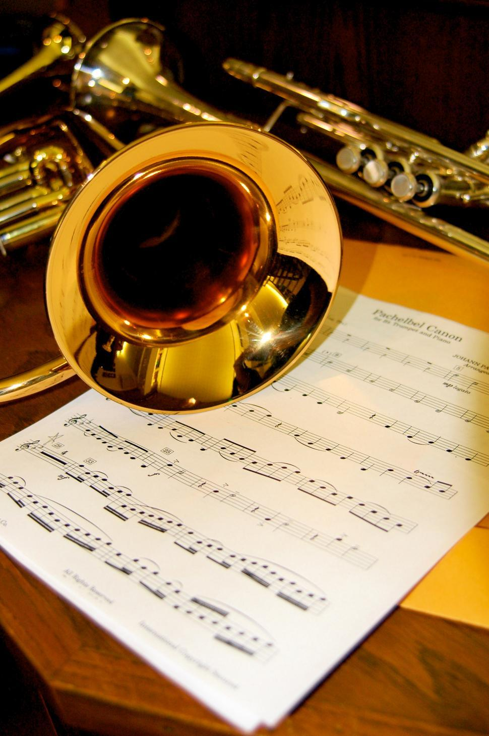 Free image of Trumpet and Music Sheet.  Bronze instrument with notes on music scales on sheet.