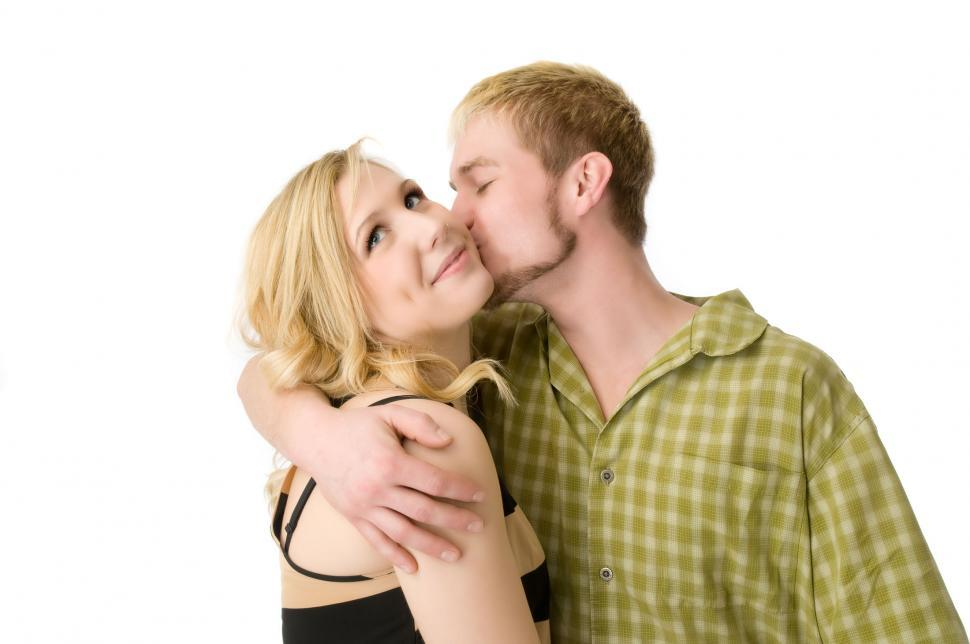 Free image of A young man kisses a young woman on the cheek.