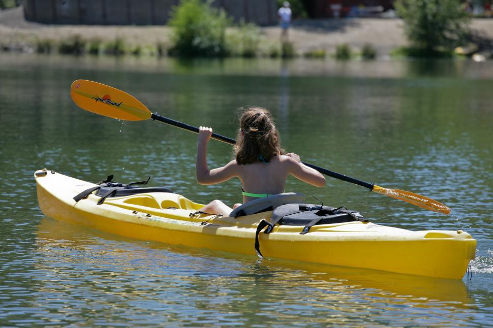 Free image of A young girl rowing around a lake.