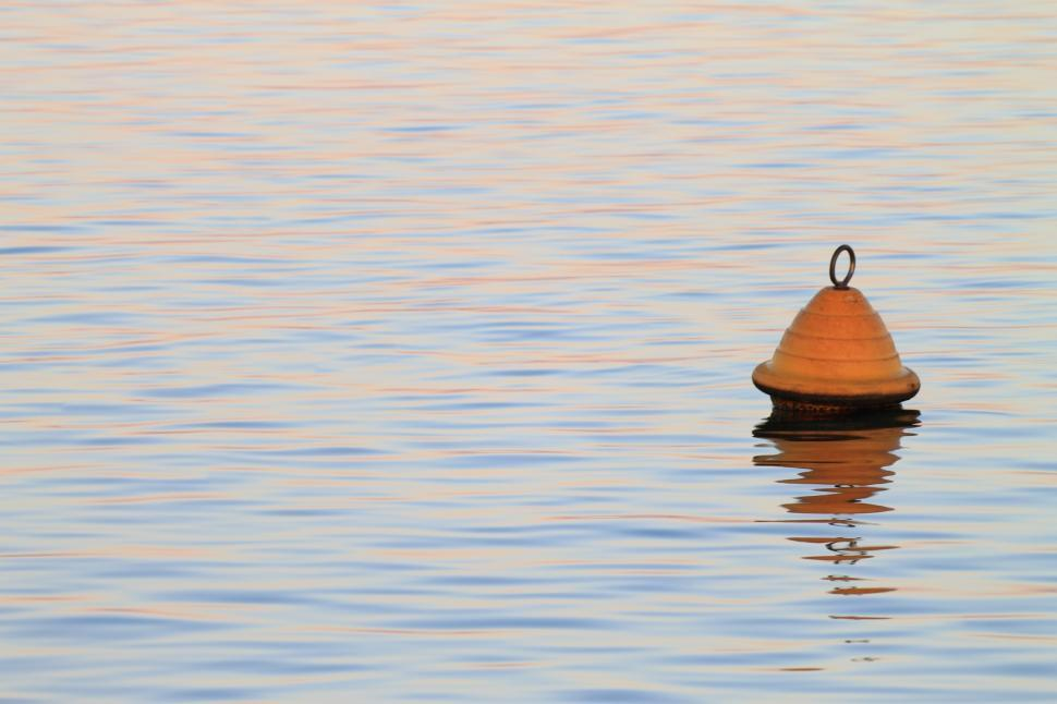 Download Free Stock HD Photo of Yellow buoy floating on calm sea Online