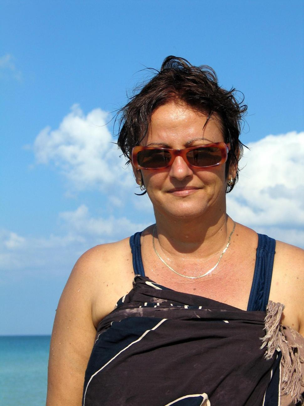Free image of Portrait of mature woman wearing sunglasses on the beach