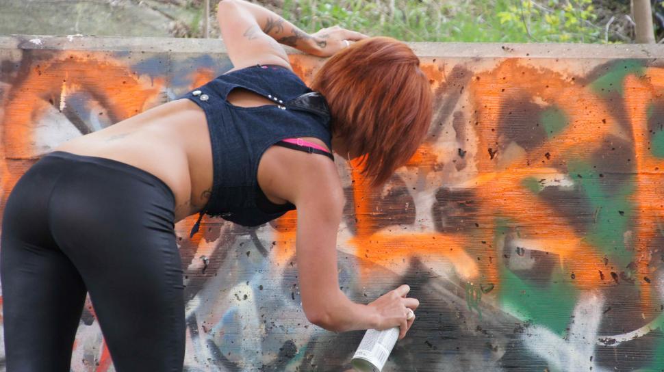 Download Free Stock HD Photo of woman Spray Paints Graffiti Online