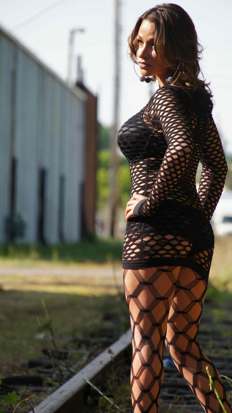 Download Free Stock HD Photo of Woman in Fishnets Stands on Train Track Online