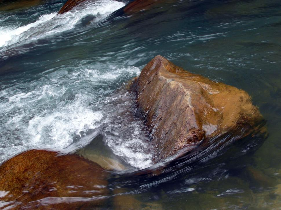 Download Free Stock HD Photo of Water rushing by smooth boulders in a river Online