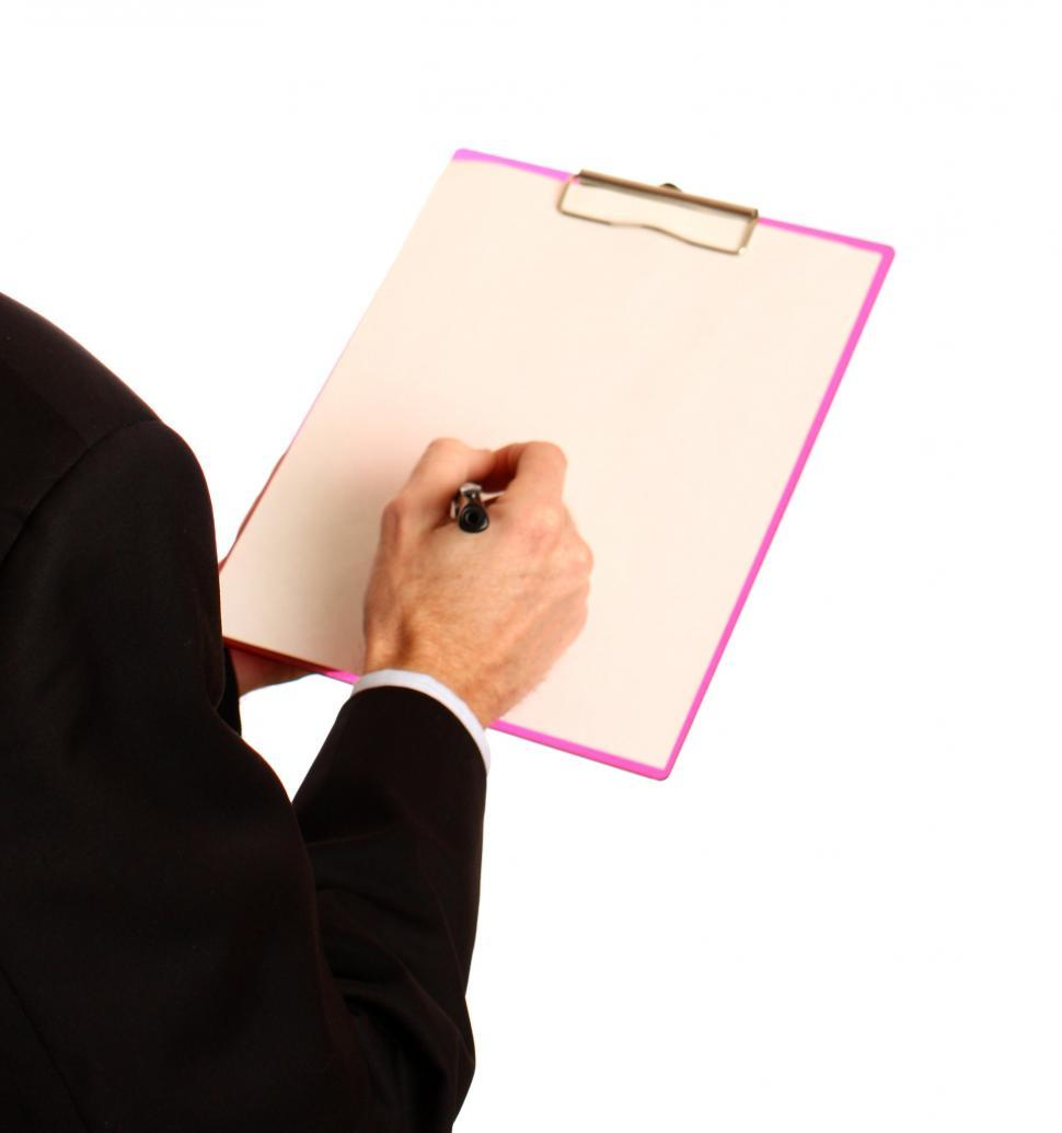 Download Free Stock HD Photo of A Young Businessman Holding A Clipboard And Pen Online