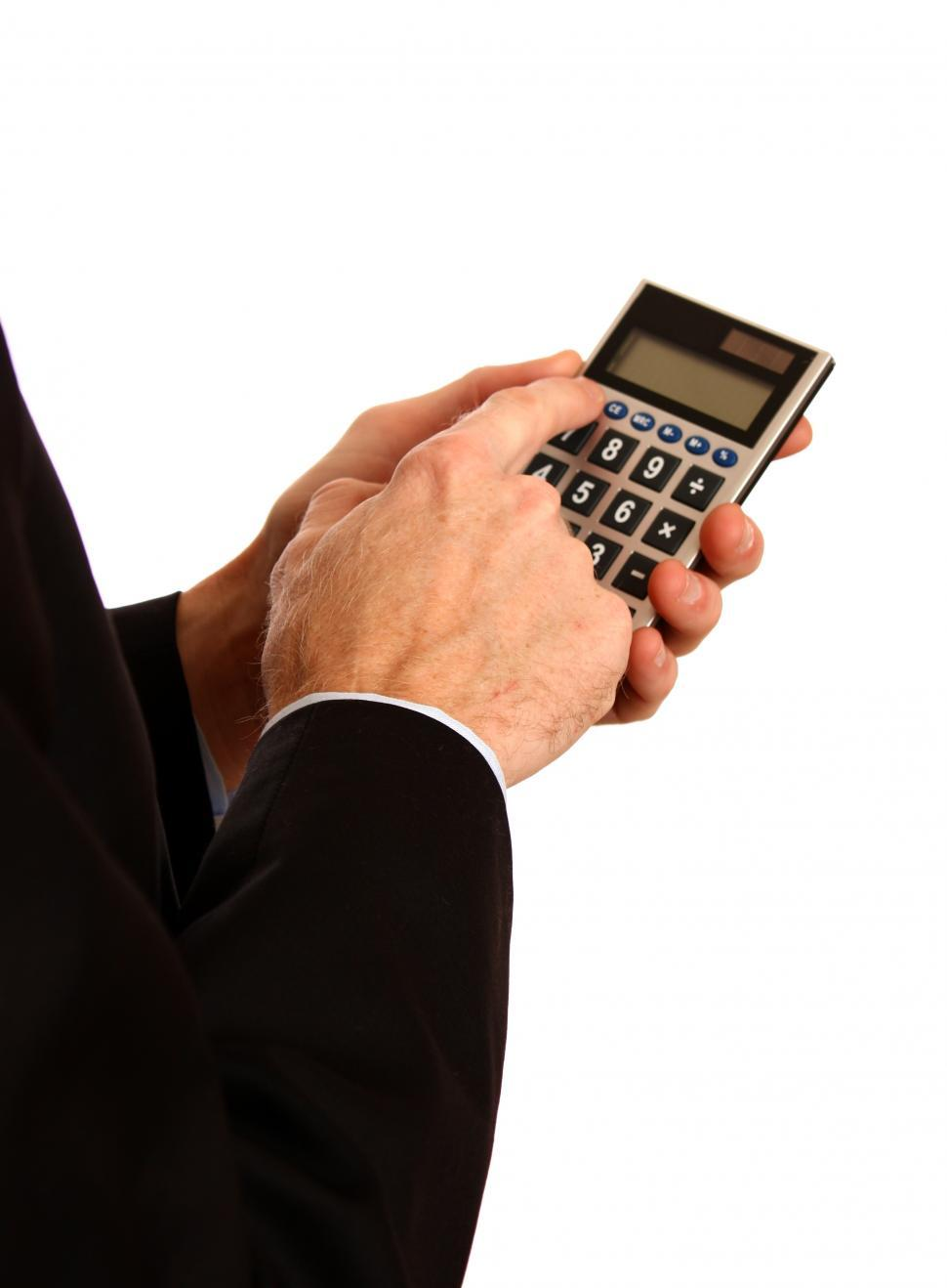 Download Free Stock HD Photo of A young businessman in a suit using a calculator Online