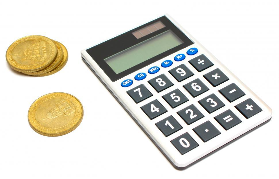 Calculator And A Stack Of Gold Coins