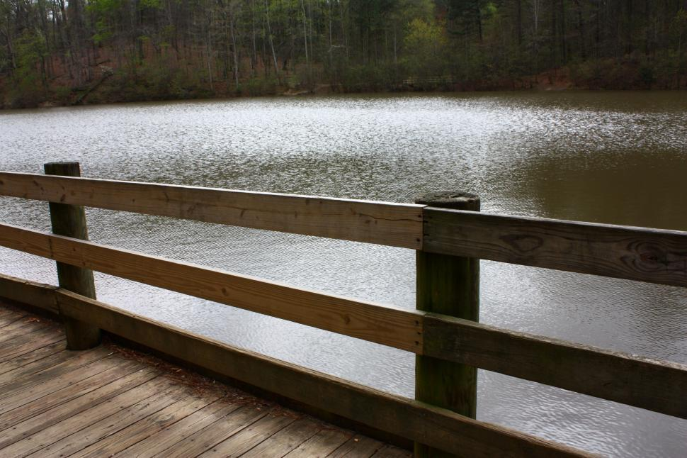 Download Free Stock HD Photo of A wooden fence by a lake Online