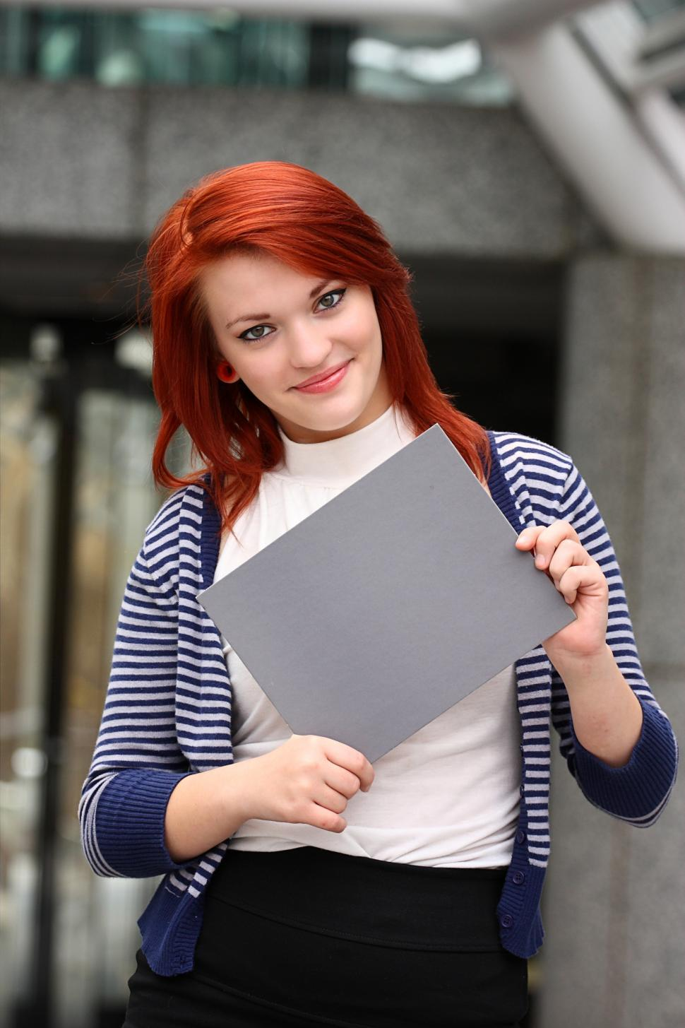Download Free Stock HD Photo of A beautiful young woman holding a blank card Online