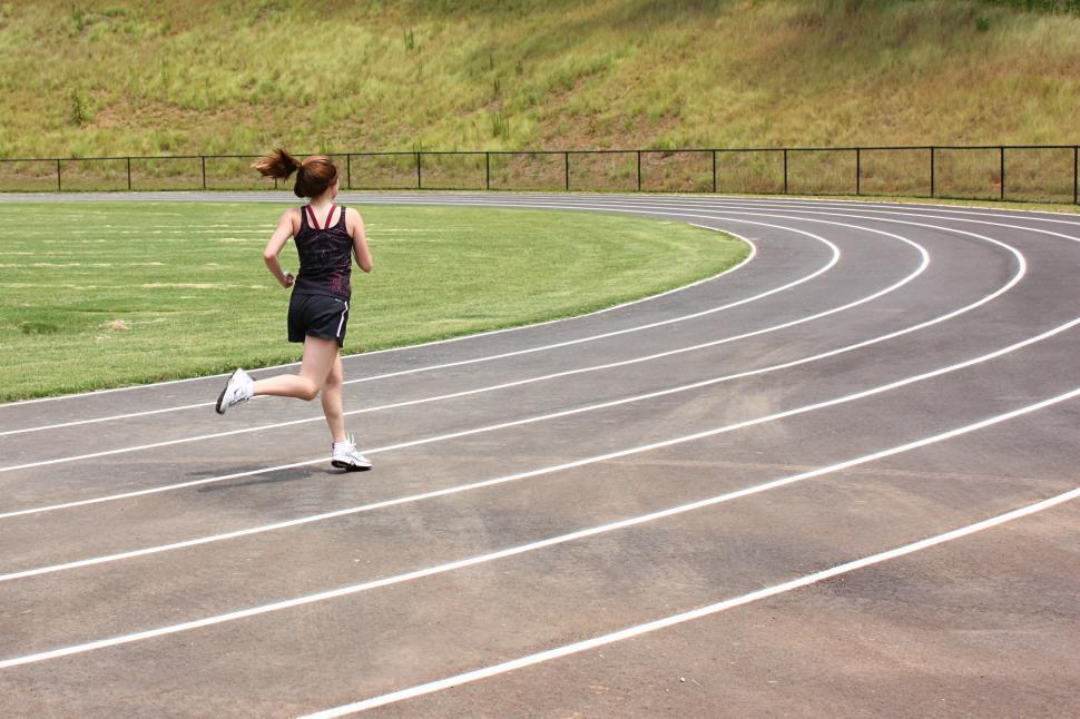 Download Free Stock HD Photo of A cute young girl running on a track field Online