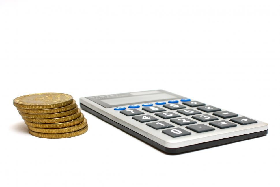 A Calculator And Stack Of Gold Coins