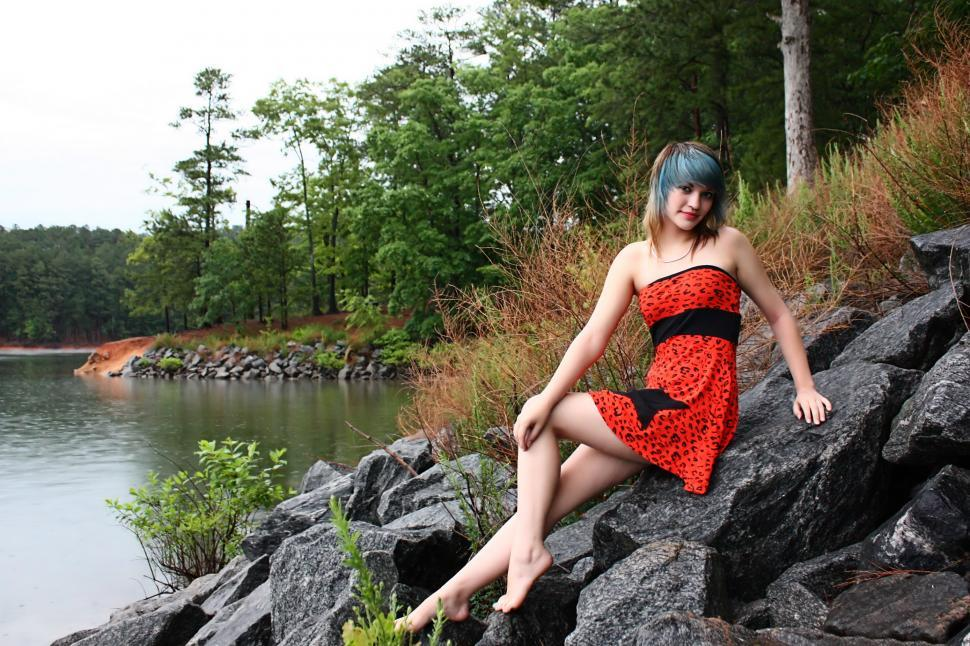 Download Free Stock HD Photo of A beautiful young woman posing in a red dress on rocks by a lake Online