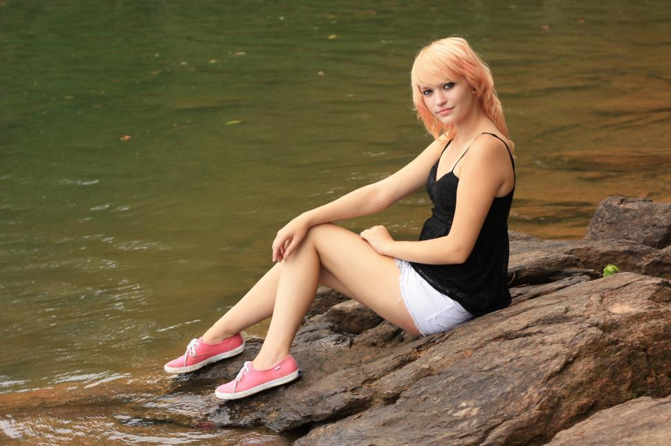 Download Free Stock HD Photo of A beautiful young woman posing on a rock by a lake Online