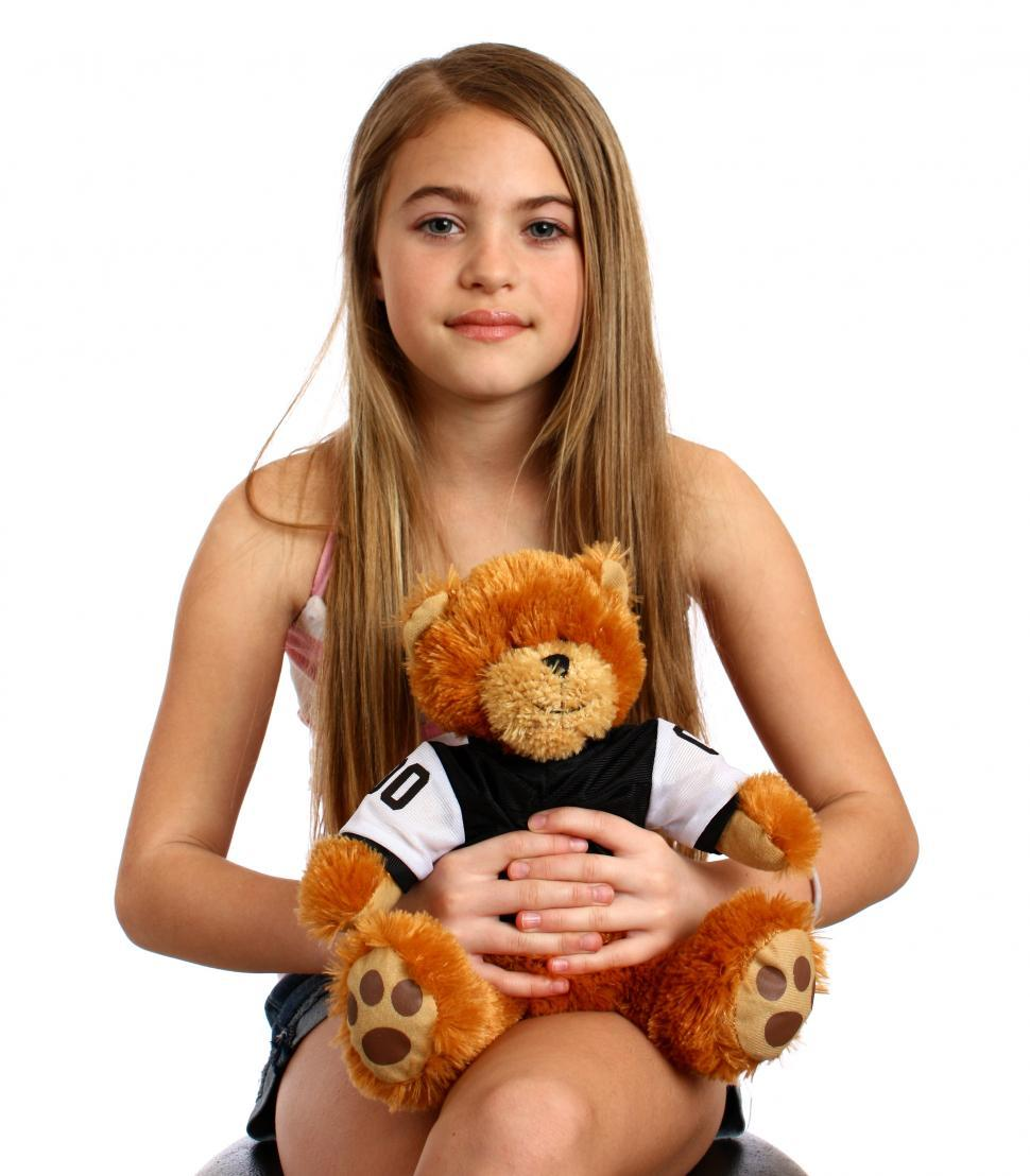 Download Free Stock HD Photo of A beautiful young girl holding a teddy bear Online