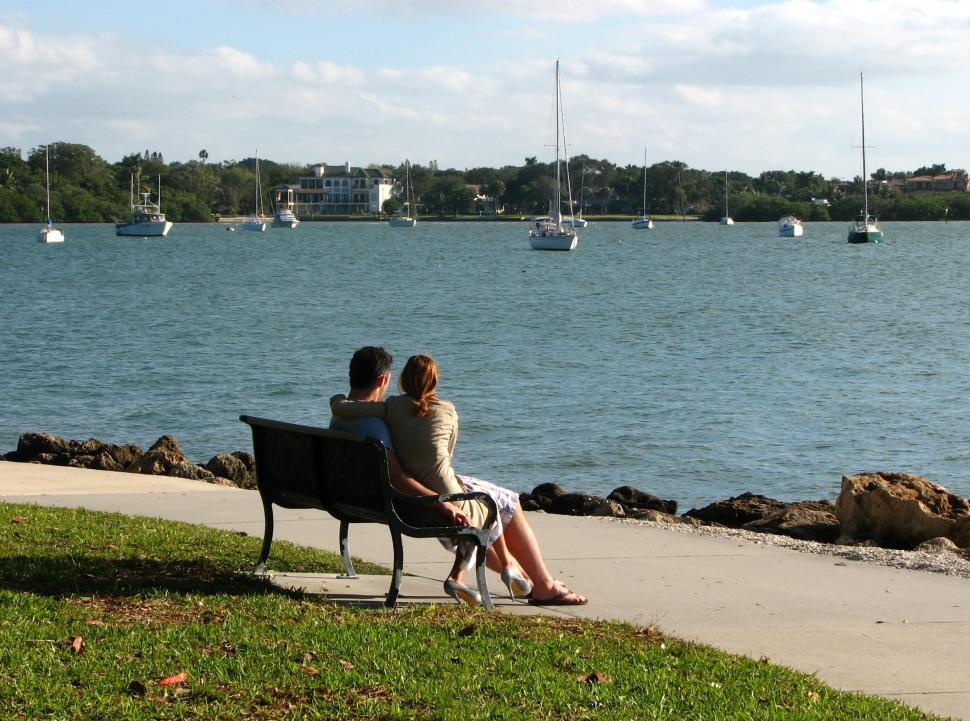 Download Free Stock HD Photo of A couple sitting on a bench overlooking the ocean Online