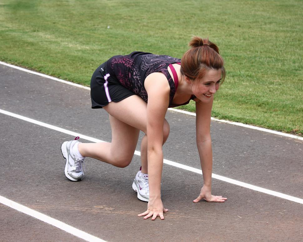 Download Free Stock HD Photo of A cute young girl on a track field preparing to race Online