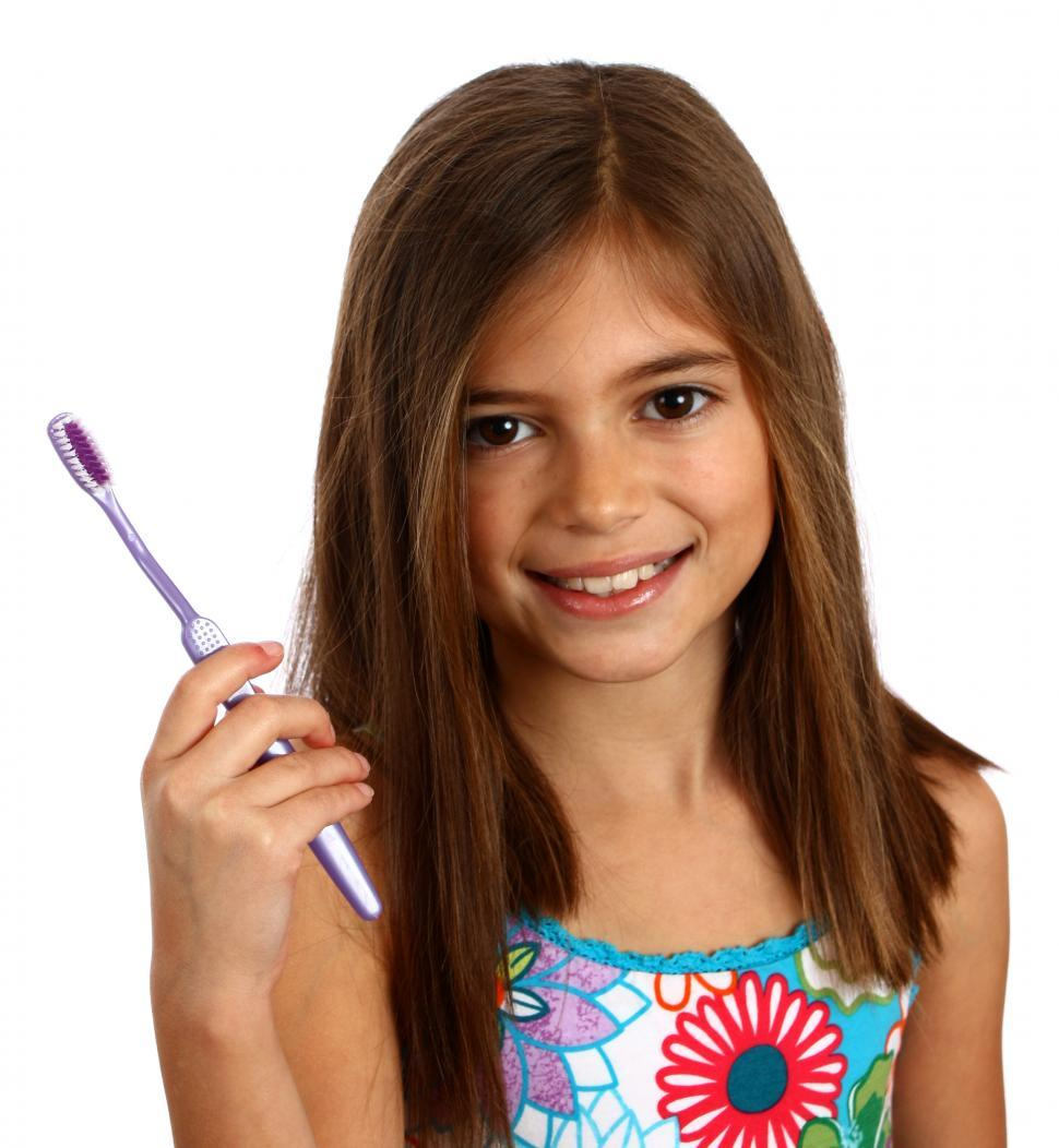 Download Free Stock HD Photo of A pretty young girl holding a toothbrush Online