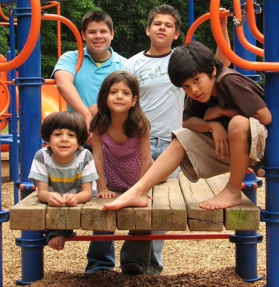 Download Free Stock HD Photo of A group of latino kids posing on a playground Online