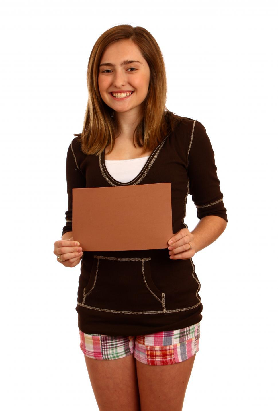 Download Free Stock HD Photo of A cute young girl posing with a blank brown sign Online