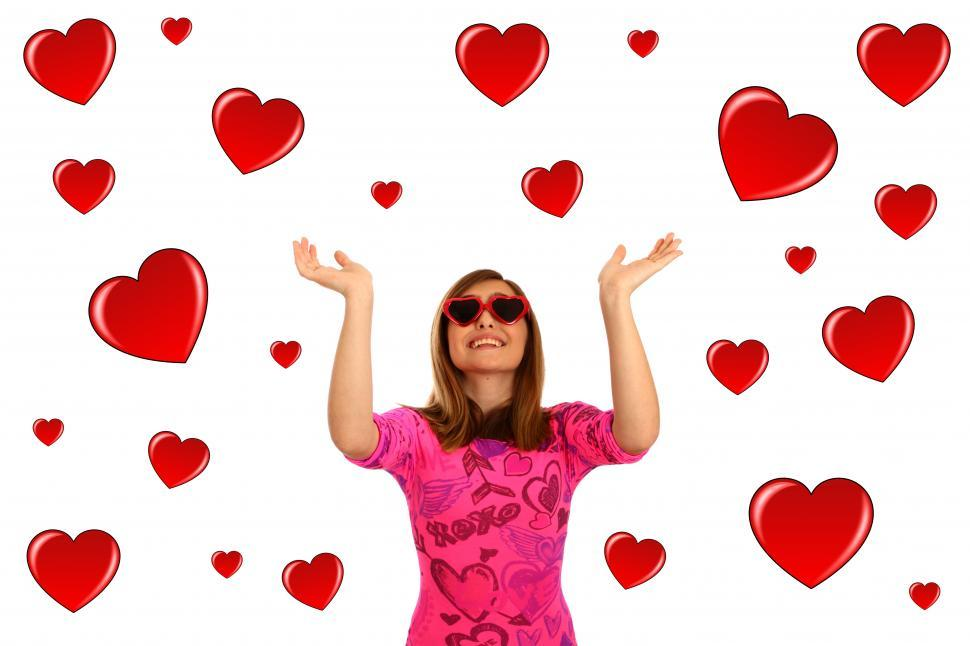 Download Free Stock HD Photo of A cute young girl dressed up for Valentines Day surrounded by hearts Online