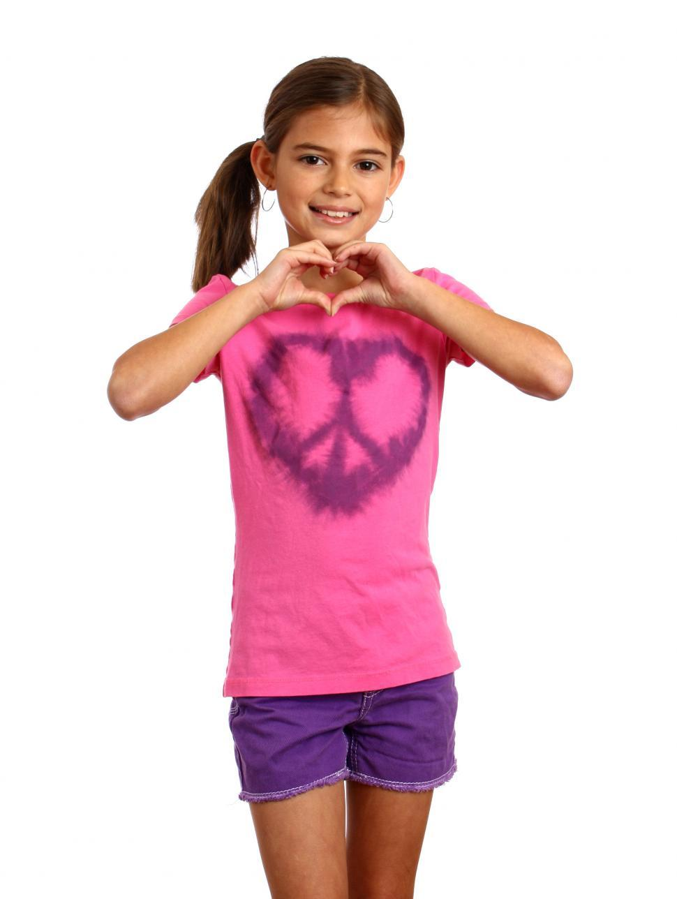 Download Free Stock HD Photo of A cute young girl making a heart symbol Online