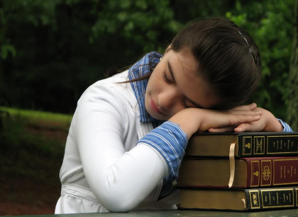 Download Free Stock HD Photo of A young schoolgirl resting her head on a stack of books Online