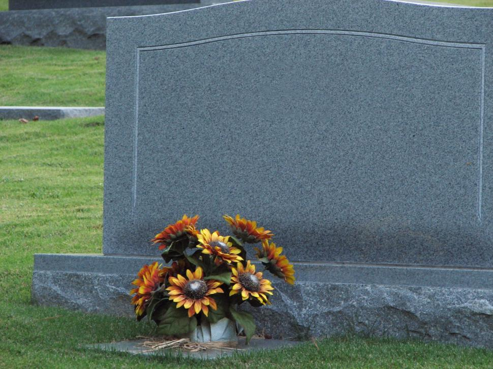 Download Free Stock HD Photo of A blank tombstone with flowers Online