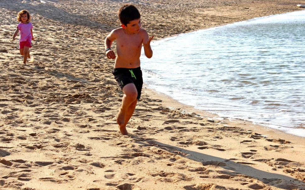 Download Free Stock HD Photo of A little boy and a little girl running on the beach Online