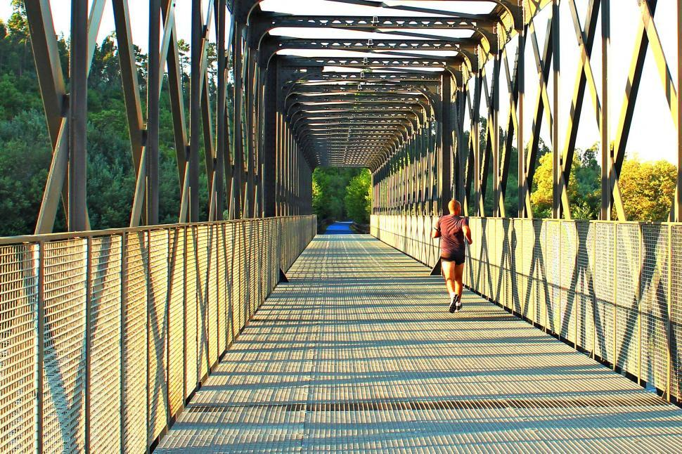 Download Free Stock HD Photo of Runner crossing a metal bridge at sunrise during morning trainin Online