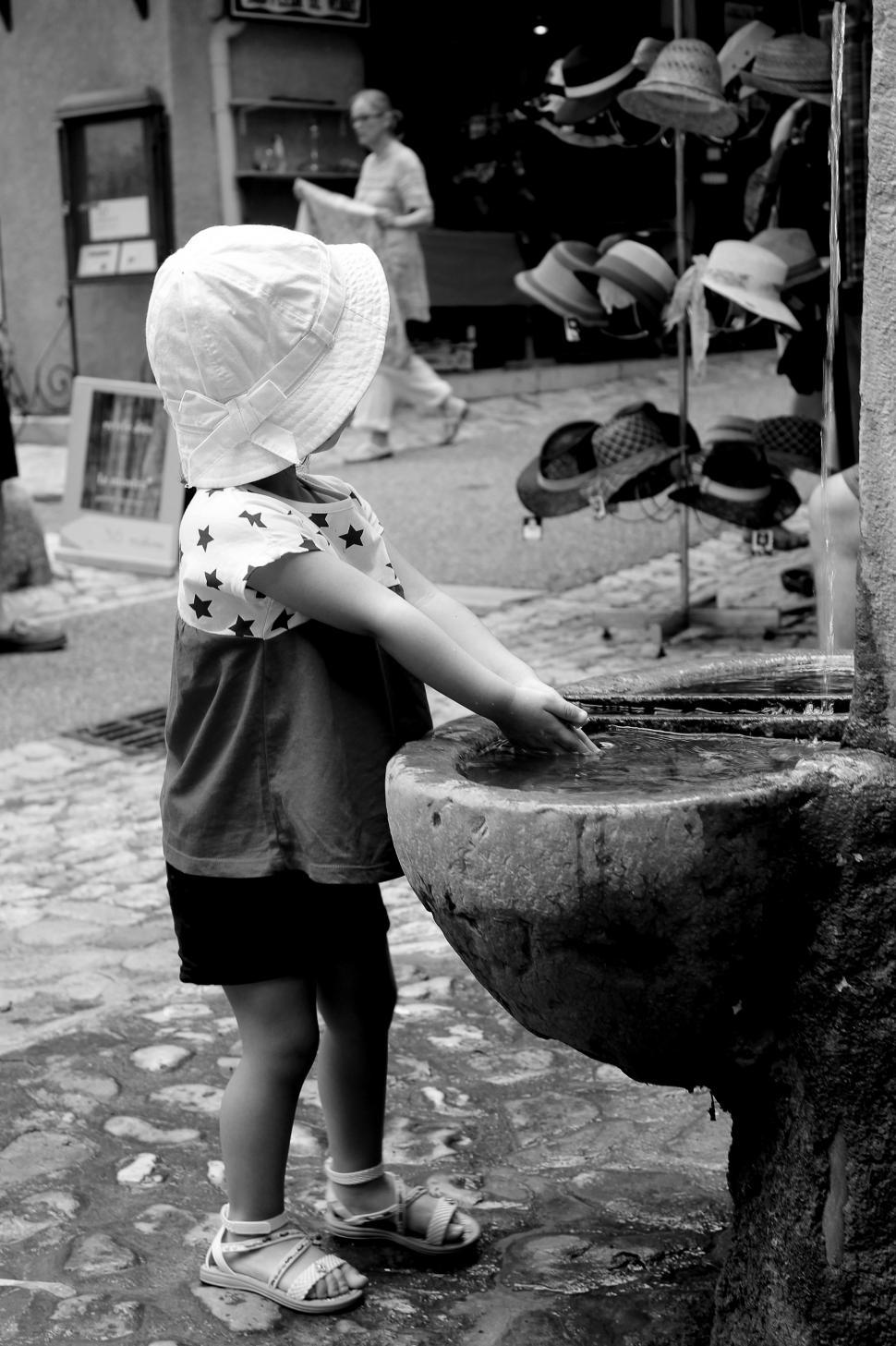 Download Free Stock HD Photo of Toddler washing her hands while observing hats for sale in Moust Online