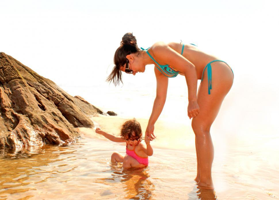 Download Free Stock HD Photo of Child bathing in a natural sea pool with the help of her mother Online