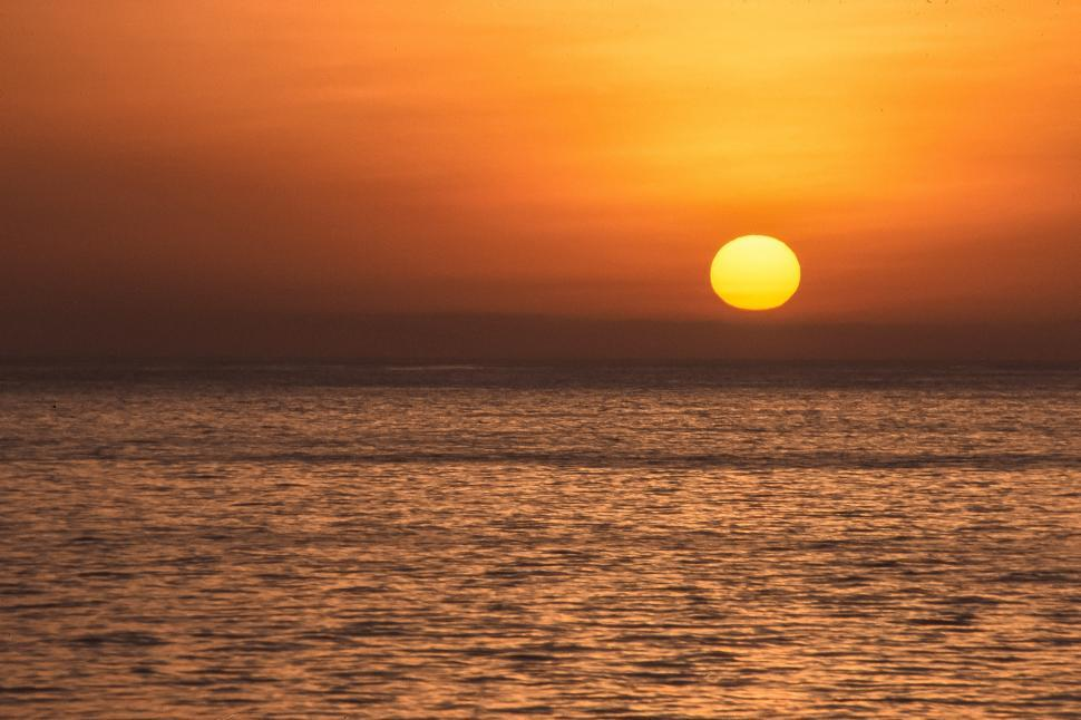 Free image of An image of a sun rising in the ocean.