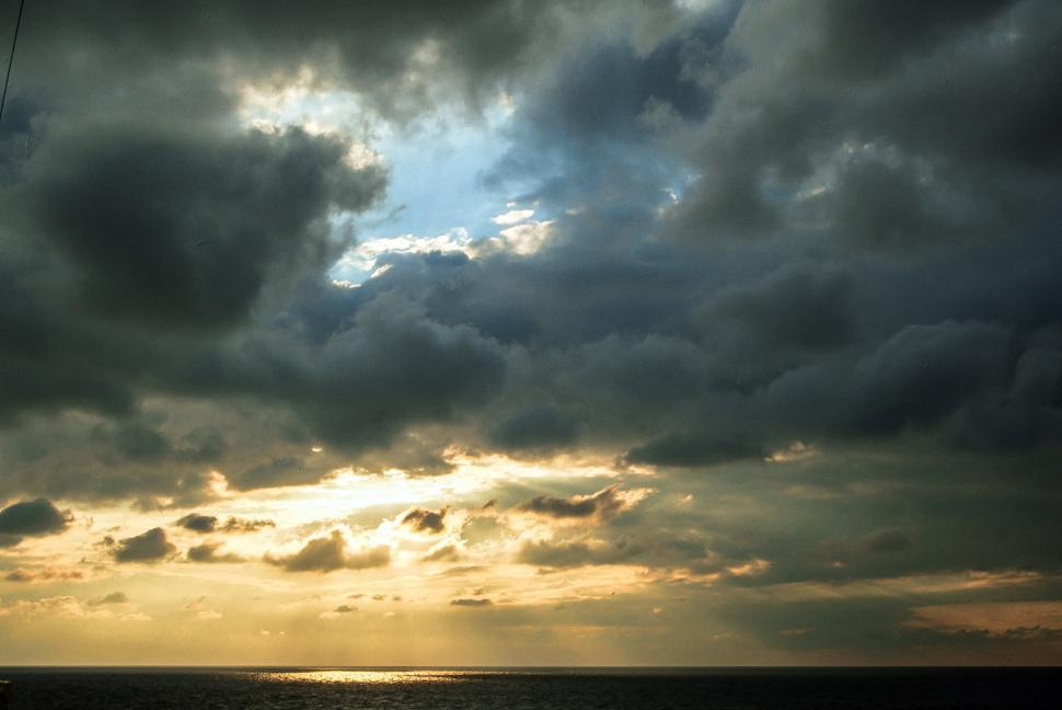Free image of Sunbeam goes through thick clouds and reflects off the water surface.