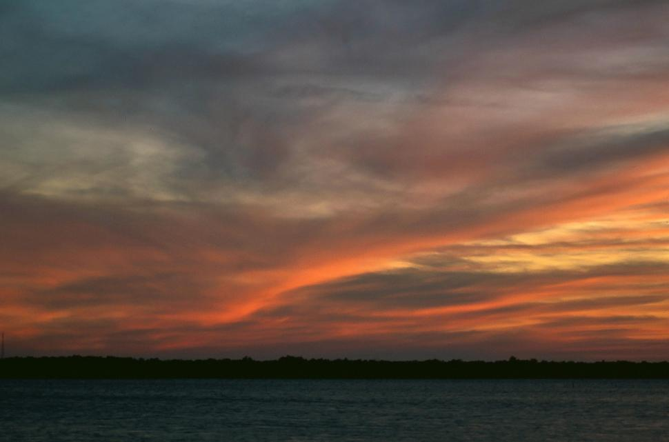 Free image of Sunset above a coast, mystical clouds are reflecting the pink light of the sun.