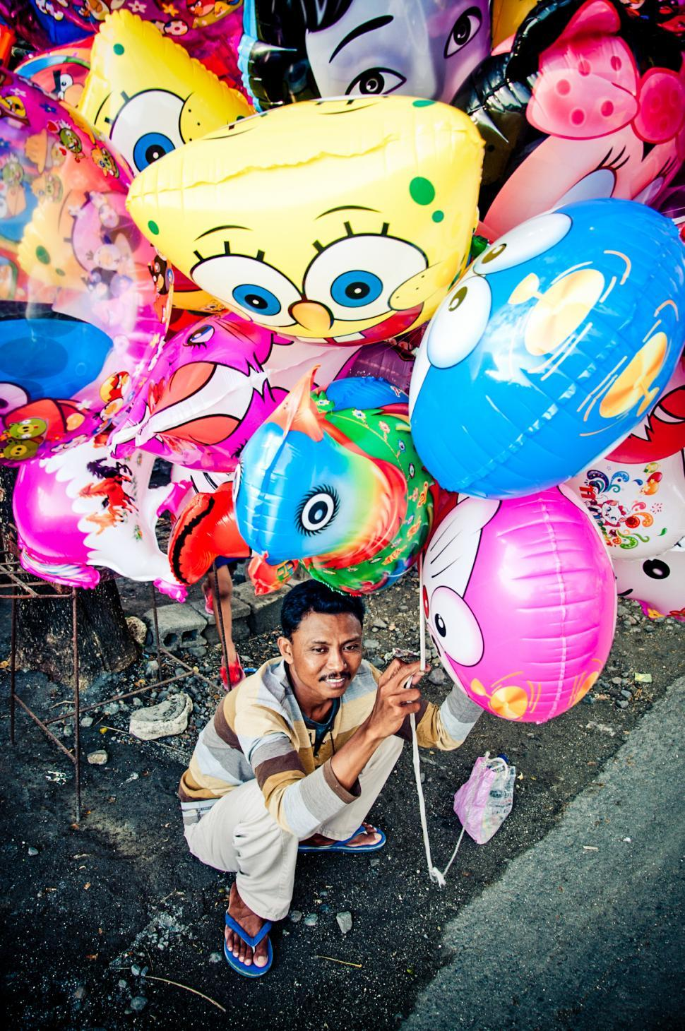 Download Free Stock HD Photo of Asian man selling balloons in the street Online